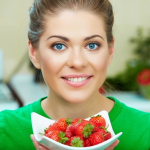 Smiling woman eating strawberry.